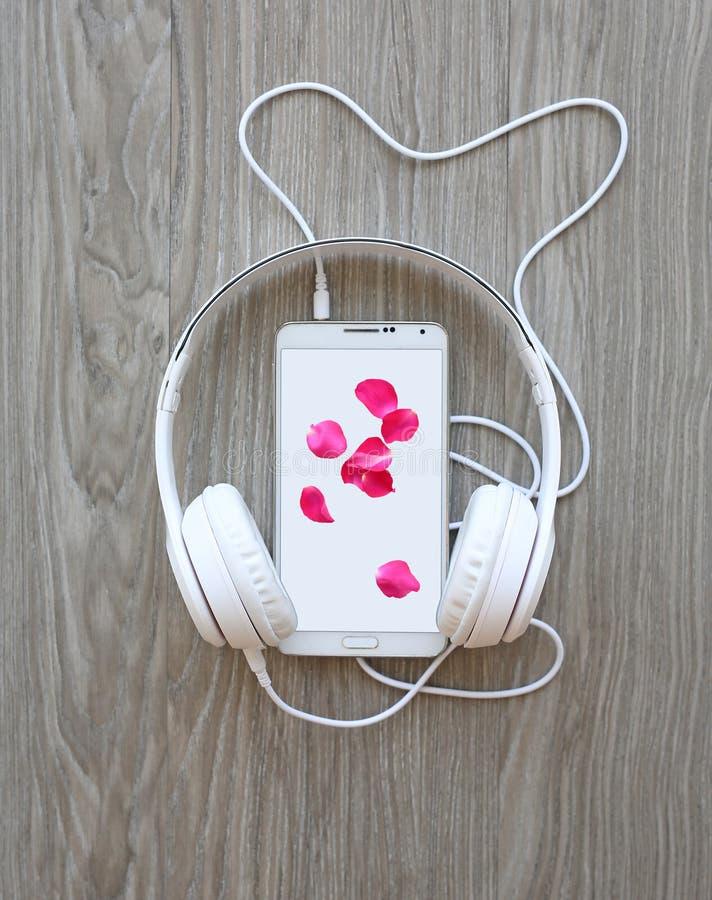 Hełmofony i smartphone z płatkami menchii róża na bielu ekranie przeciw drewnianemu tłu fotografia stock