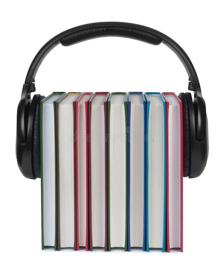 Hełmofony na książkach na białym tle. obraz stock