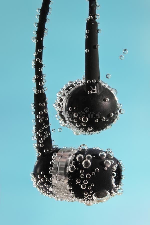 Hełmofony pod wodą odizolowywającą na błękitnym tle. Studio strzał. zdjęcia stock
