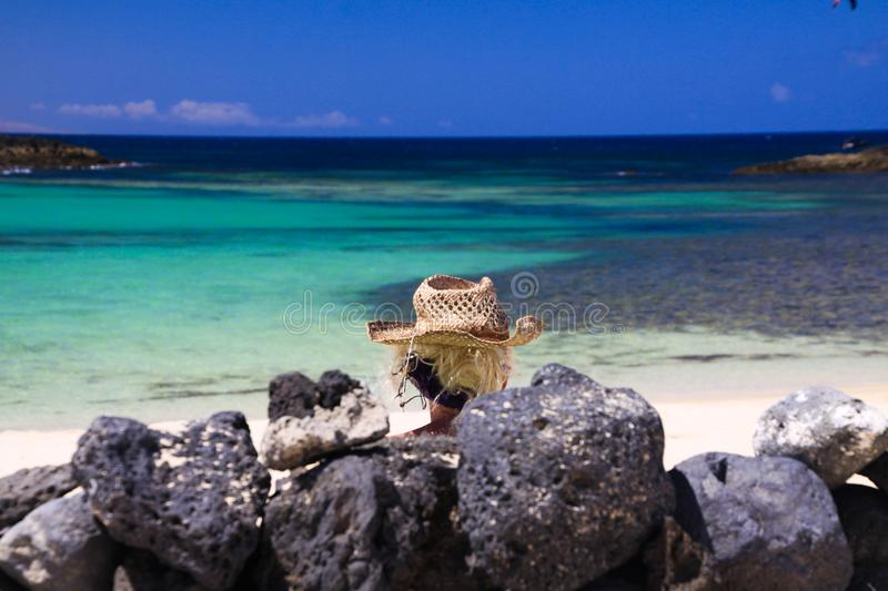 Head of blonde woman with straw hat sitting behind wall of piled natural rocks on beach with turquoise ocean - Fuerteventura, El royalty free stock images
