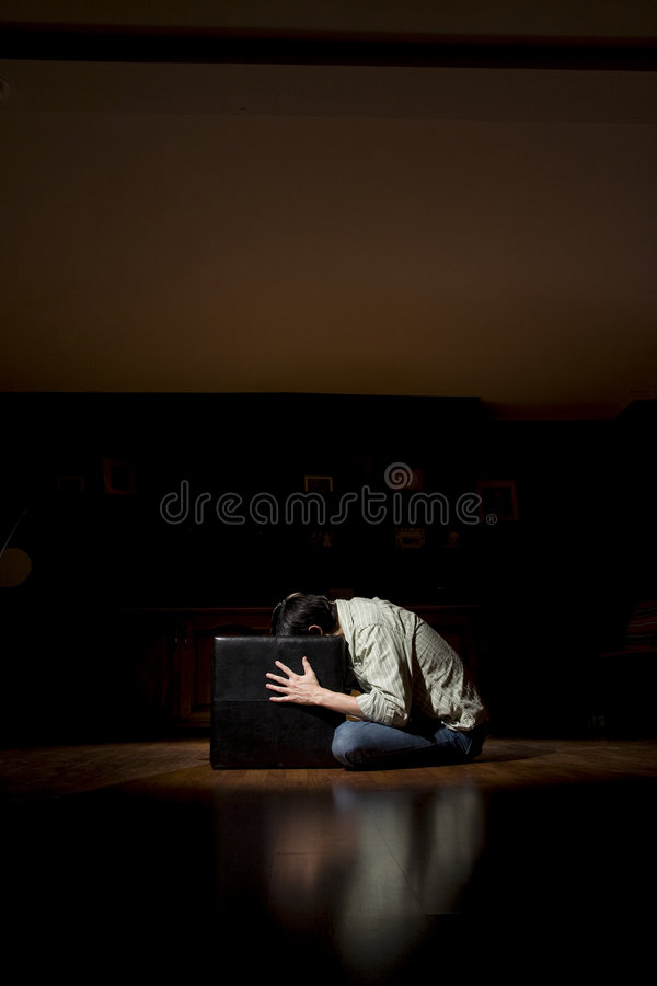 Head in the Box. Man sitting in the floor with his head in a black box stock image
