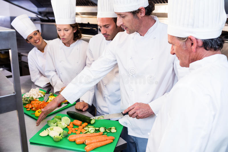 Head chef teaching his colleagues how to slice vegetables stock photo