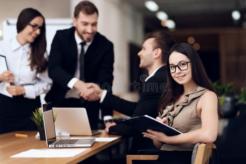 The head of the company shakes hands with another employee during the meeting. stock image