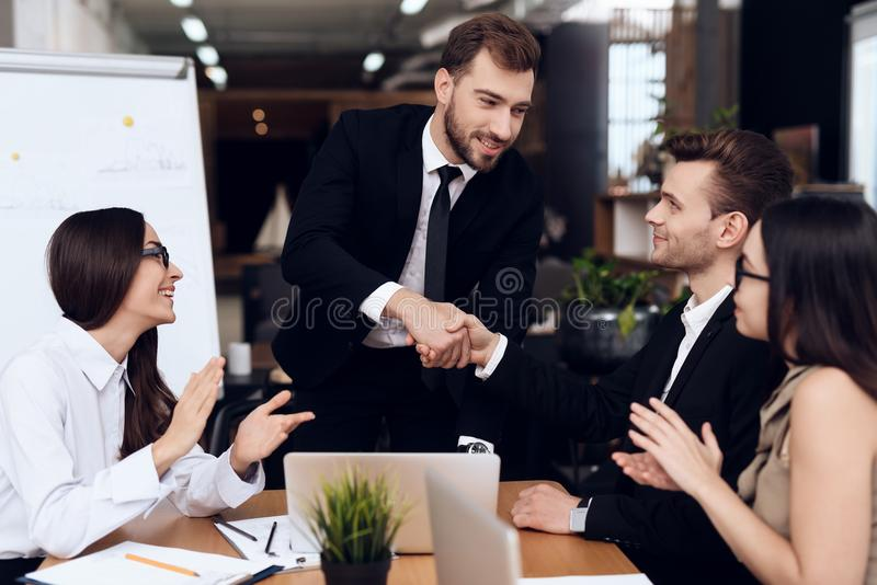 The head of the company shakes hands with another employee during the meeting. royalty free stock photos