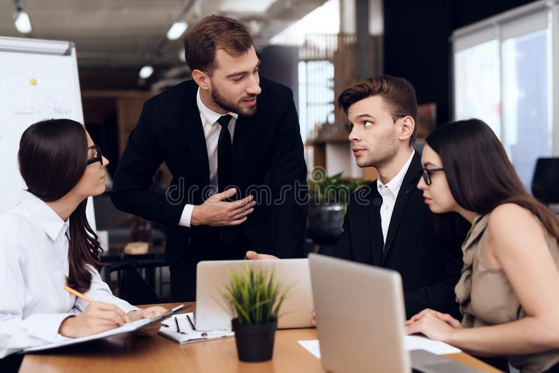 The head of the company talks with other employees during the meeting. stock photo