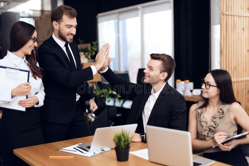 The head of the company talks with other employees during the meeting. They are dressed in business suits. They talk about business stock photos