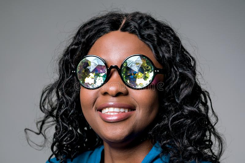 The head of a Dark-skinned beautiful beautiful young woman in funny round holographic glasses. royalty free stock images