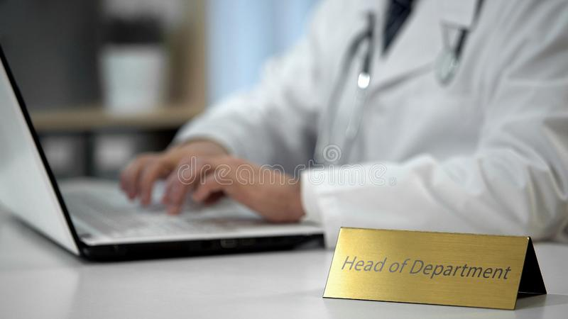 Head of department filling out medical papers, doctor prescribing medication royalty free stock image