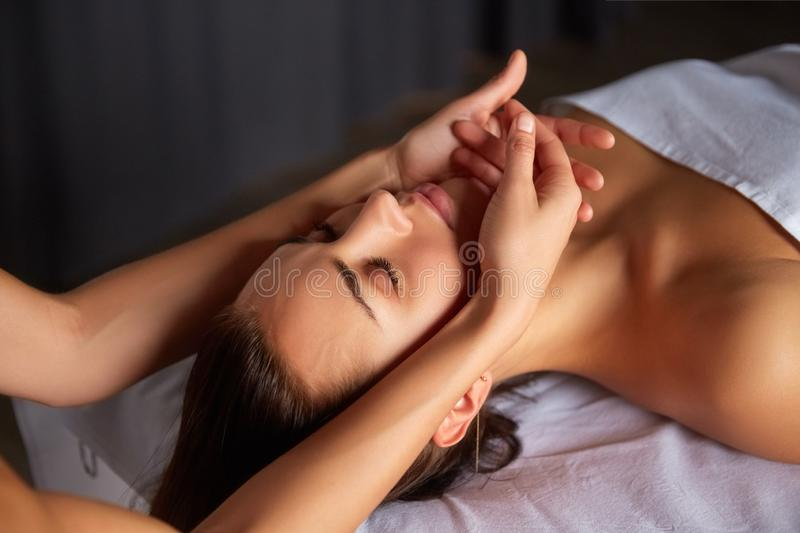 Head and face massage in spa salon. Close-up of female enjoying relaxing head and face massage made by masseuse with forearms and cubits in cosmetology spa stock photos