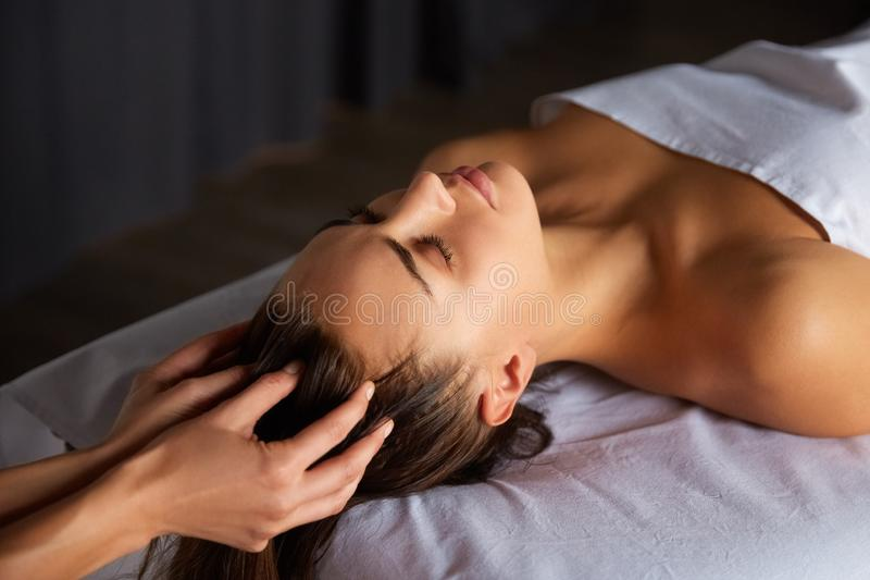Head and face massage in spa salon. Close-up of female enjoying relaxing head and face massage made by masseuse with forearms and cubits in cosmetology spa stock photography