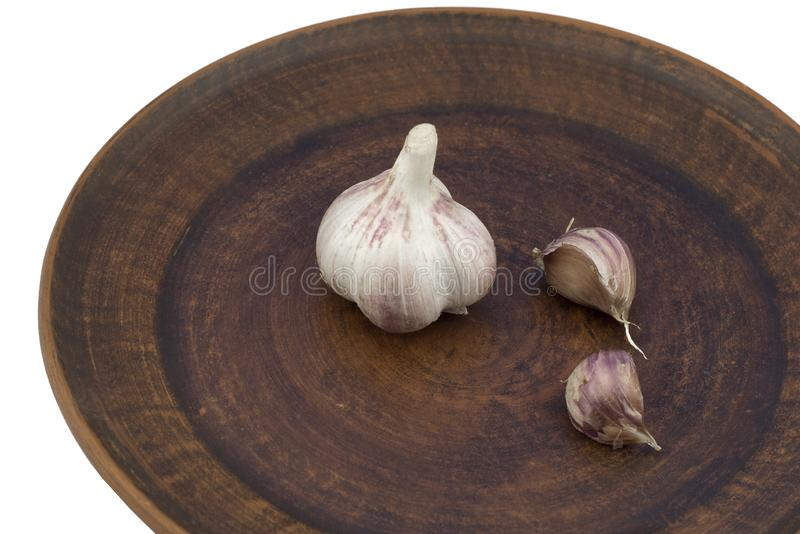 Head of garlic on a brown clay plate isolated on white background close-up. Isolate head of garlic and two cloves are lying on a brown clay plate on a white royalty free stock photography