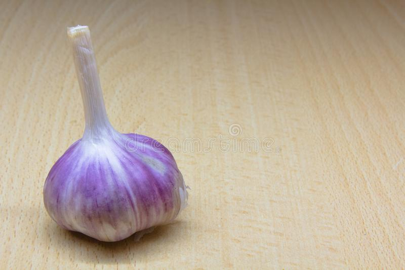 Head of garlic close-up against the background of a wooden table stock image