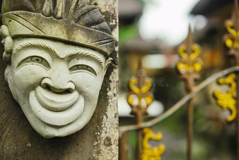 Head of a Hindu deity stone statue of a person with a smile on the background of a fence. Travels in Bali Indonesia royalty free stock photo