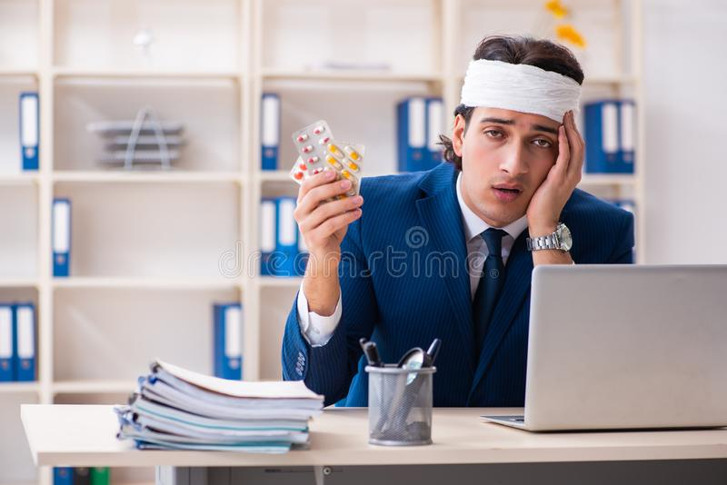Head injured male employee working in the office stock image