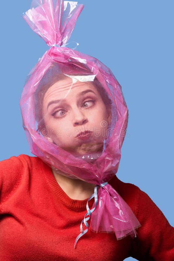 Head inside candy wrapper. Fun girl with head inside candy wrapper on blue background stock photo