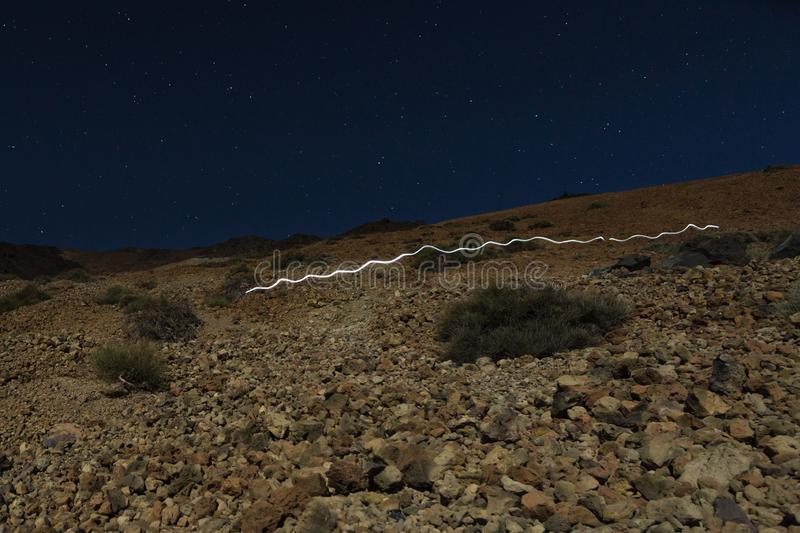 Head lamp light trail on volcano Teide stock images