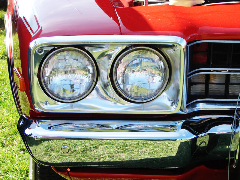 Head lights chrome bumper of a red car. Close-up on the headlights and the chrome bumper of a Hot rod bright red car at a meet show royalty free stock images