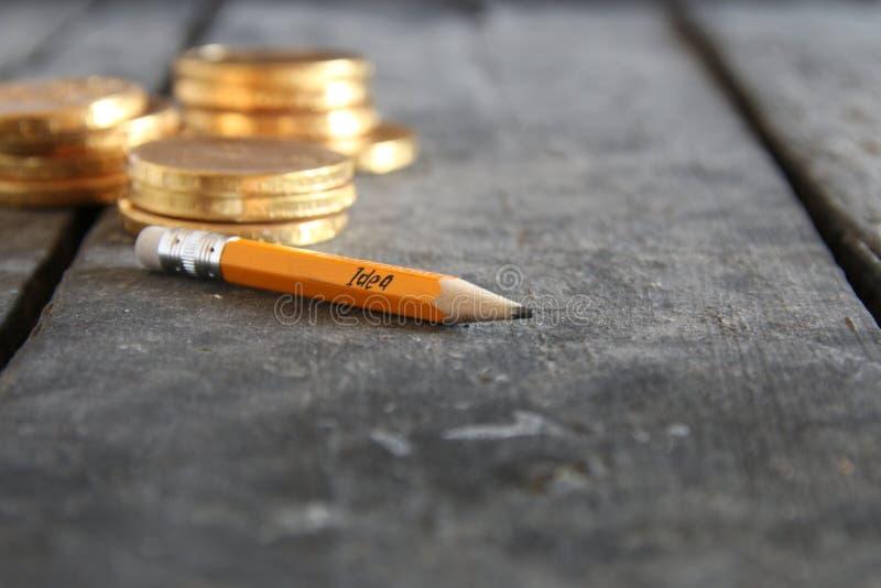Head människa för lampa mot begreppsmässig bakgrund Blyertspenna och guld- mynt arkivbild