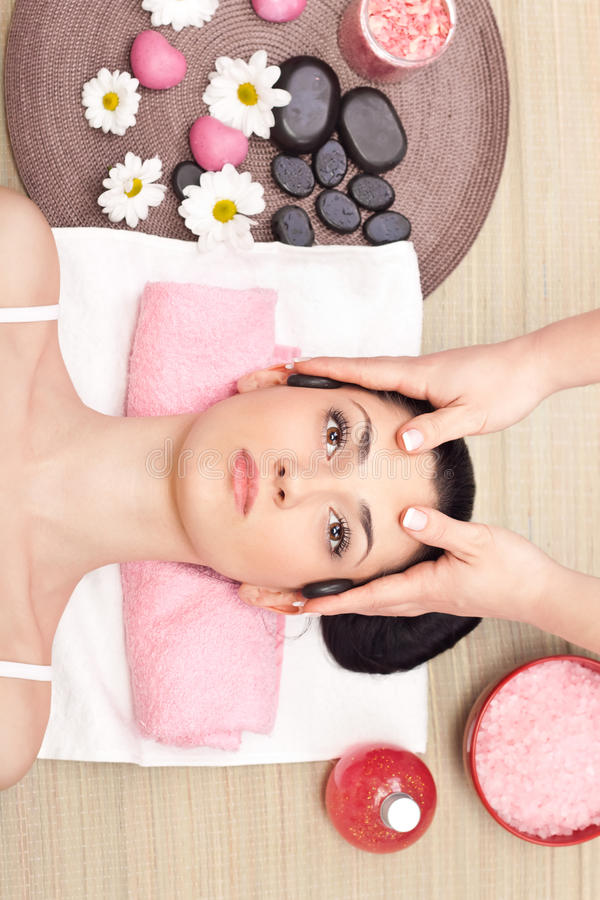 Head massage in a spa center. Young relaxed woman receiving a head massage at spa center stock photography