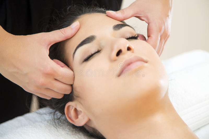 Head massage. Young woman having a face massage stock image