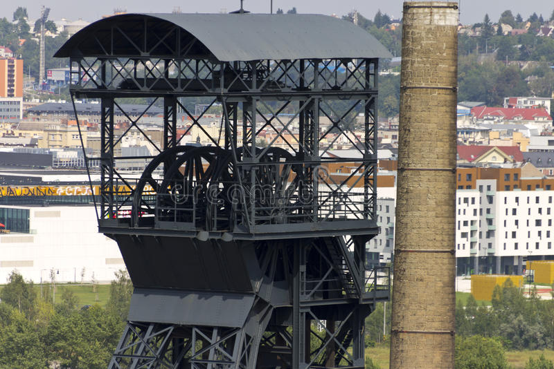 Head of the mining tower and a chimney with Ostrava center in the background. Mining tower and a chimney of Vítkovice Iron and Steel Works, Ostrava, Czech stock photo