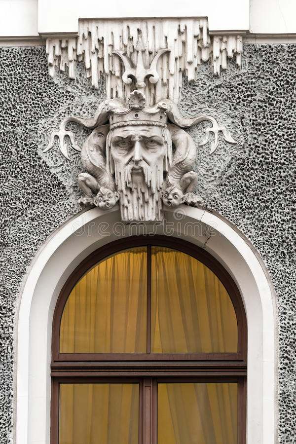 Head of Neptune in the decoration of the house in Riga. Head of Neptune in the crown and around the marine reptiles in the bas-relief of a house in Riga, Latvia stock photo