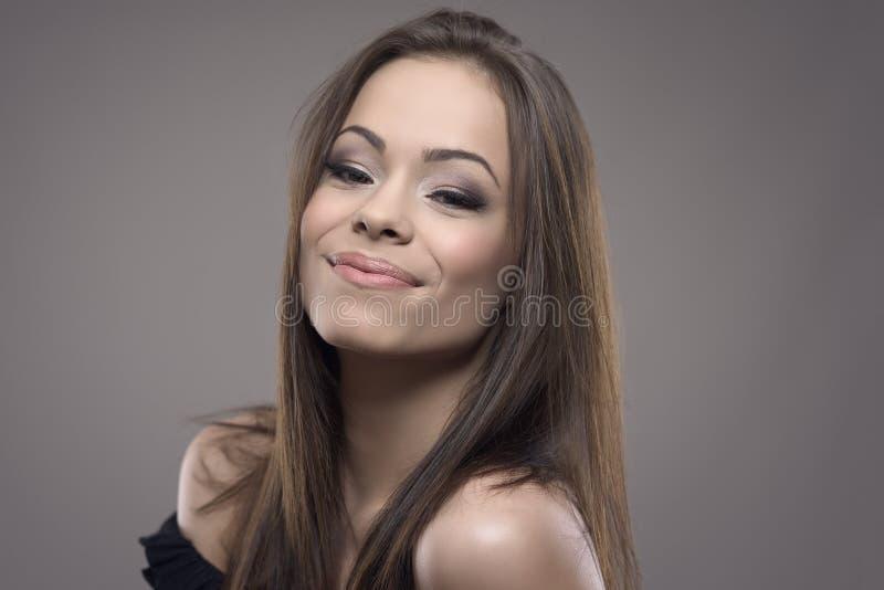 Head och skuldrahorisontalstående av den tonårs- kvinnan för nätt ung brunett som ler och ser kameran arkivfoto