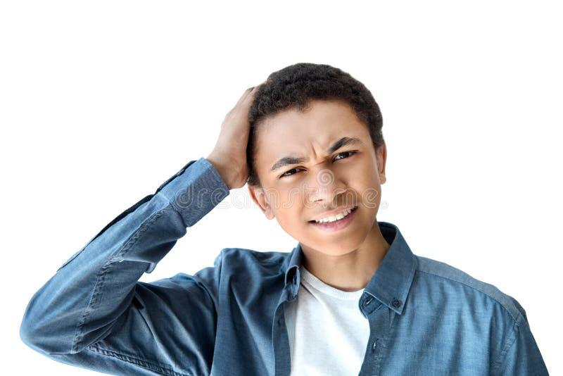head och skuldraskott av den tonåriga pojken för emotionell afrikansk amerikan med handen på huvudet som ser kameran royaltyfri foto