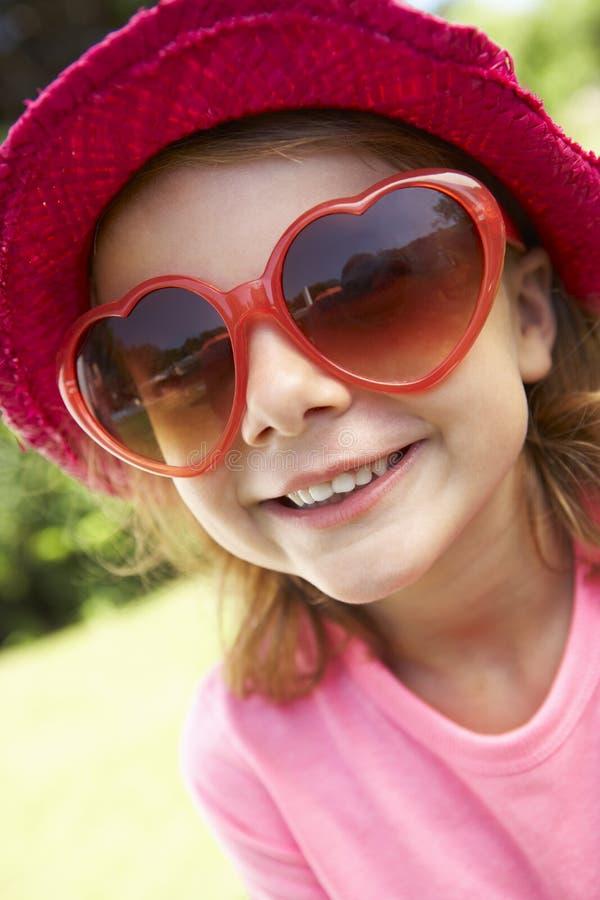 Head och skuldrastående av flickan som bär rosa Straw Hat arkivfoton