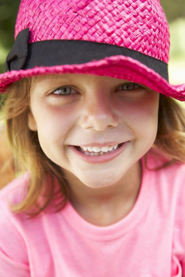 Head och skuldrastående av flickan som bär rosa Straw Hat royaltyfria foton