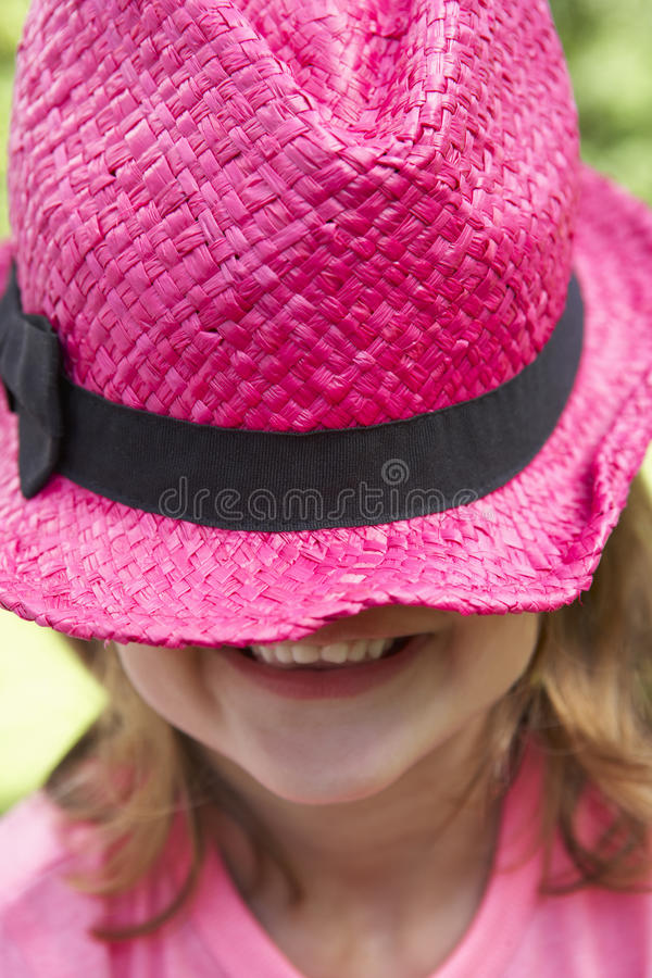 Head och skuldrastående av flickan som bär rosa Straw Hat royaltyfri bild