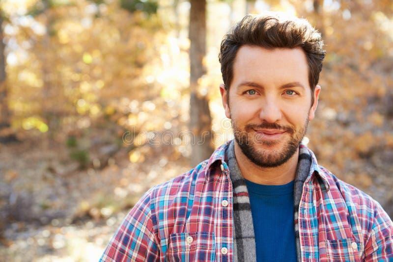 Head och skuldrastående av mannen i Autumn Woodland arkivbilder