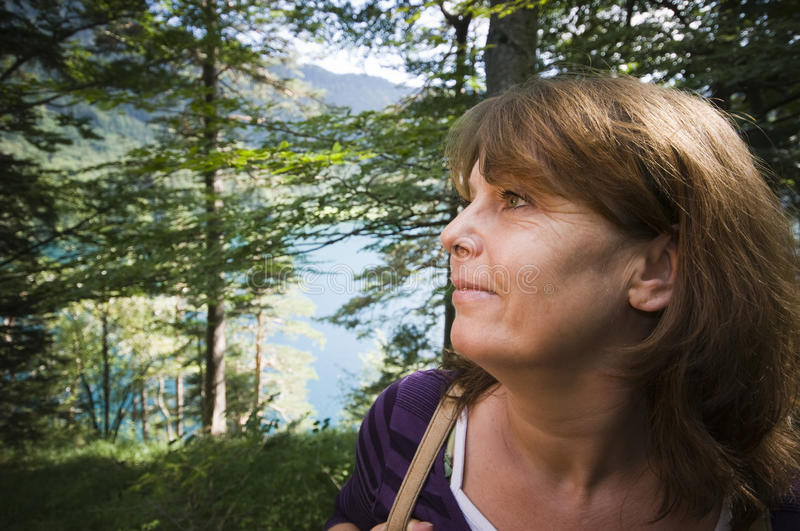 Head portrait by the lake. Profile head portrait of a woman middle age in the forest in front of a lake with flowers during daylight hours royalty free stock image