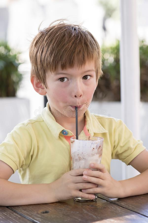 Head portrait of lovely and sweet young kid 7 or 8 years old in yellow shirt enjoying happy drinking ice cream smoothie milk shak royalty free stock images