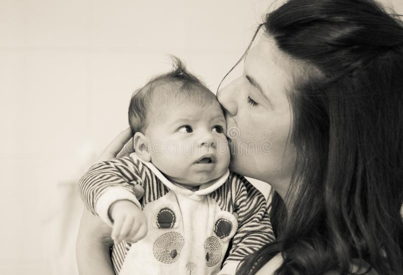 Head portrait of mom kissing her newborn with love royalty free stock images