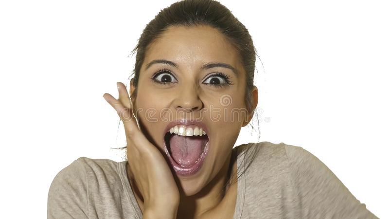 Head portrait of young happy and excited hispanic woman 30s in surprise and astonished face expression eyes and mouth wide open is. Olated on white background in royalty free stock images