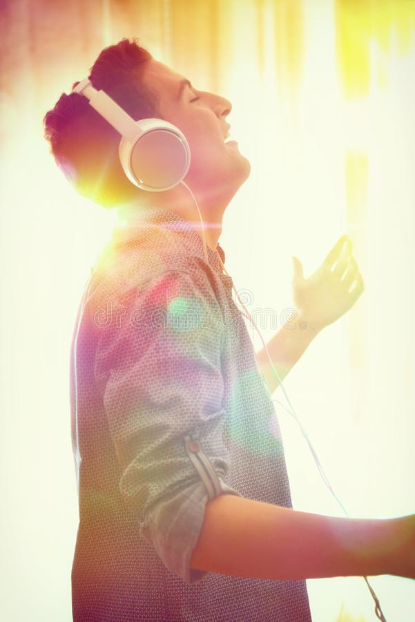 Head profile teenager listening to music and dancing multicolored lights. Head profile teenager listening to music with headsets and dancing in the living room stock images