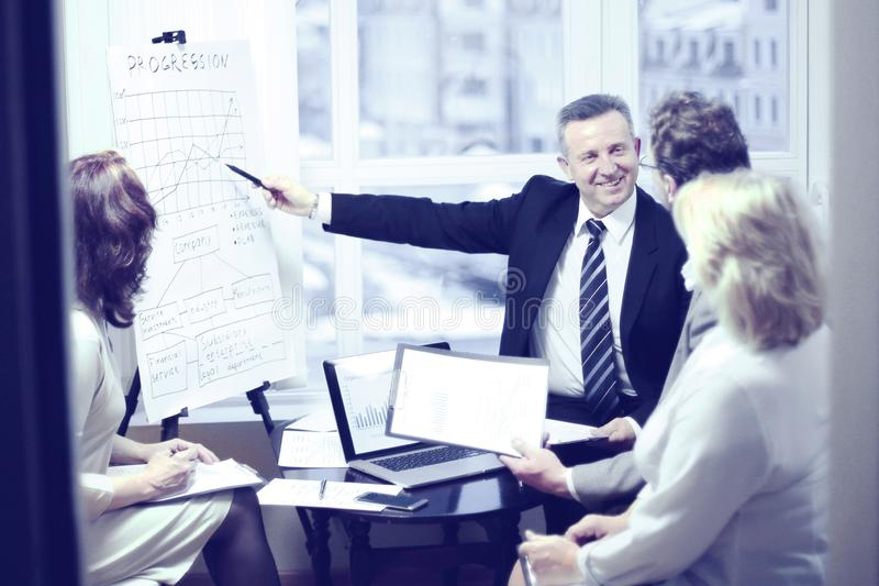 Head of the project, showing on a flip chart financial data. stock image