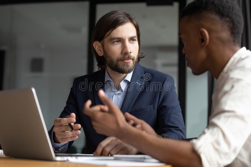Focused businessman listening to young african american employee. Head shot close up focused businessman listening to young african american employee stock photos