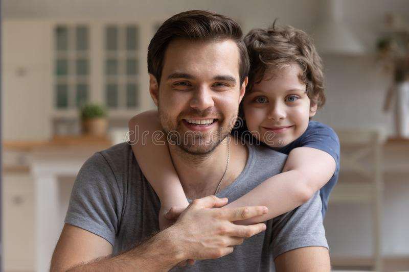 Happy little cute boy hugging smiling young father. stock photo