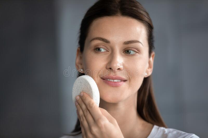 Head shot smiling woman cleaning skin with facial cleansing sponge royalty free stock images