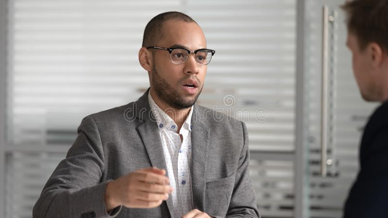Focused african american businessman coming to agreement with partner. stock photo