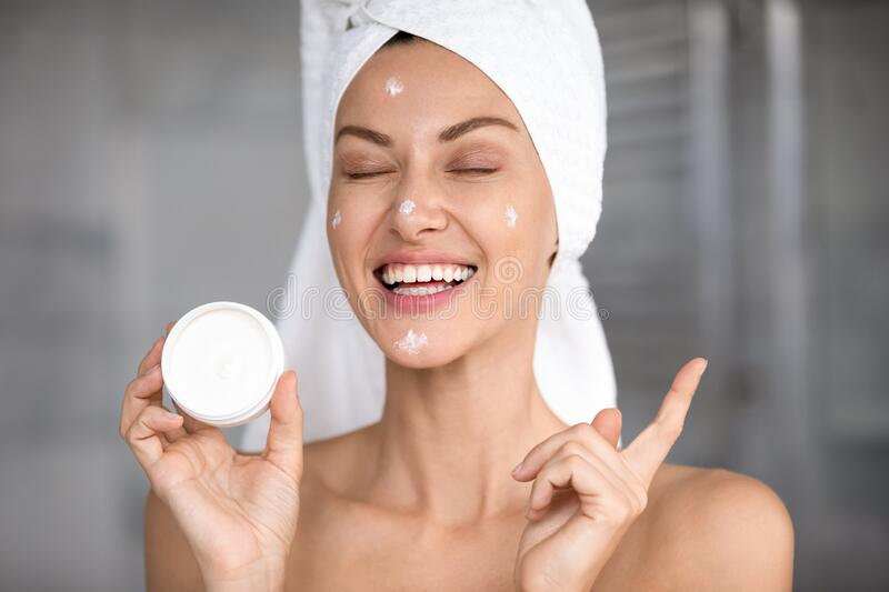 Head shot laughing funny beautiful woman holding face cream stock photography