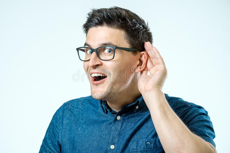 Head shot of man trying listen gossip or news. Isolated on grey. Head shot of man, hand to ear gesture trying secretly listen gossip or conversation or news stock image