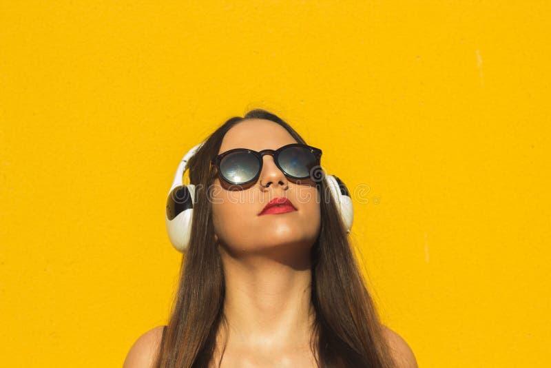 Head shot of a model listening music in headphones stock photos