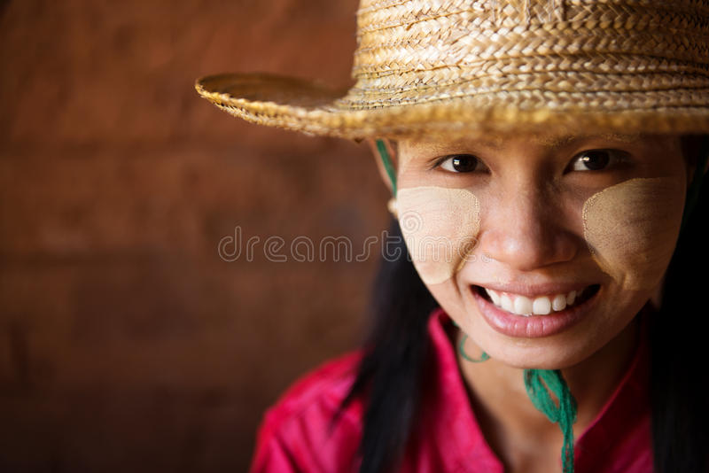 Head shot Myanmar girl. Portrait of beautiful young traditional Myanmar girl with straw hat smiling. Close up head shot stock photo
