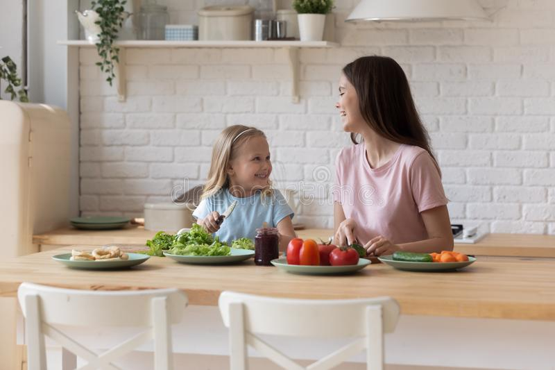 Laughing millennial woman communicating with small daughter while cooking together. royalty free stock photography