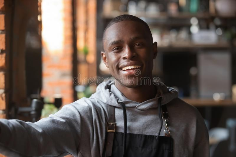 Head shot portrait of African American smiling waiter taking selfie stock photography