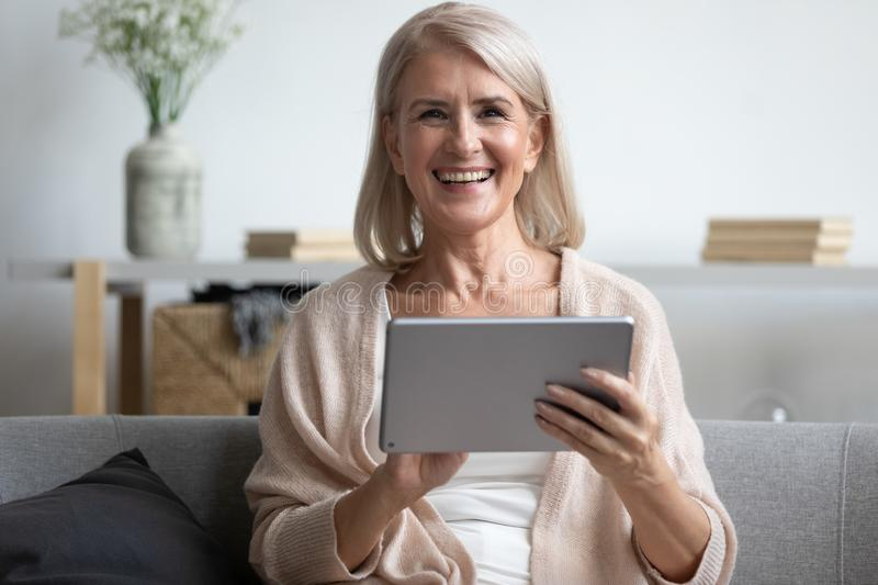 Happy mature woman using computer tablet, laughing at funny joke stock photography