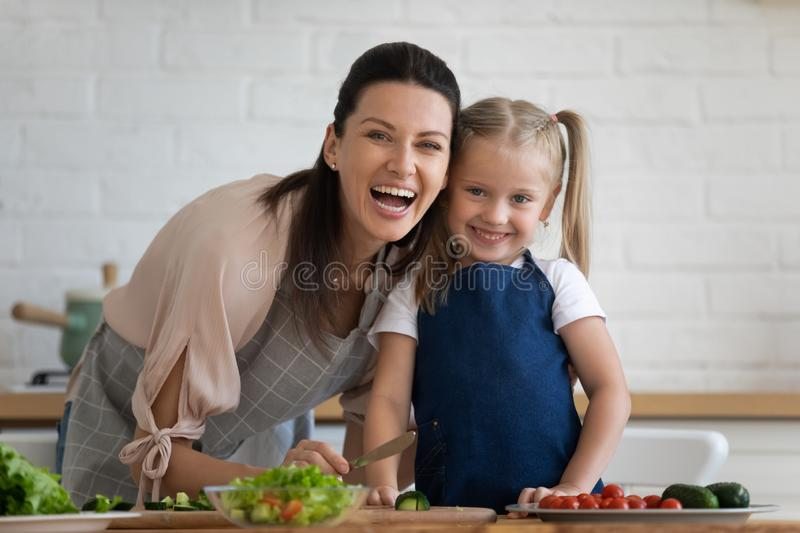 Head shot portrait excited mother and little daughter in kitchen stock image